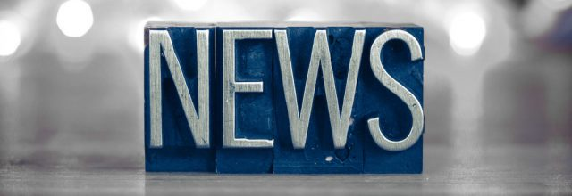 The word NEWS written in vintage metal letterpress type on a soft backlit background.